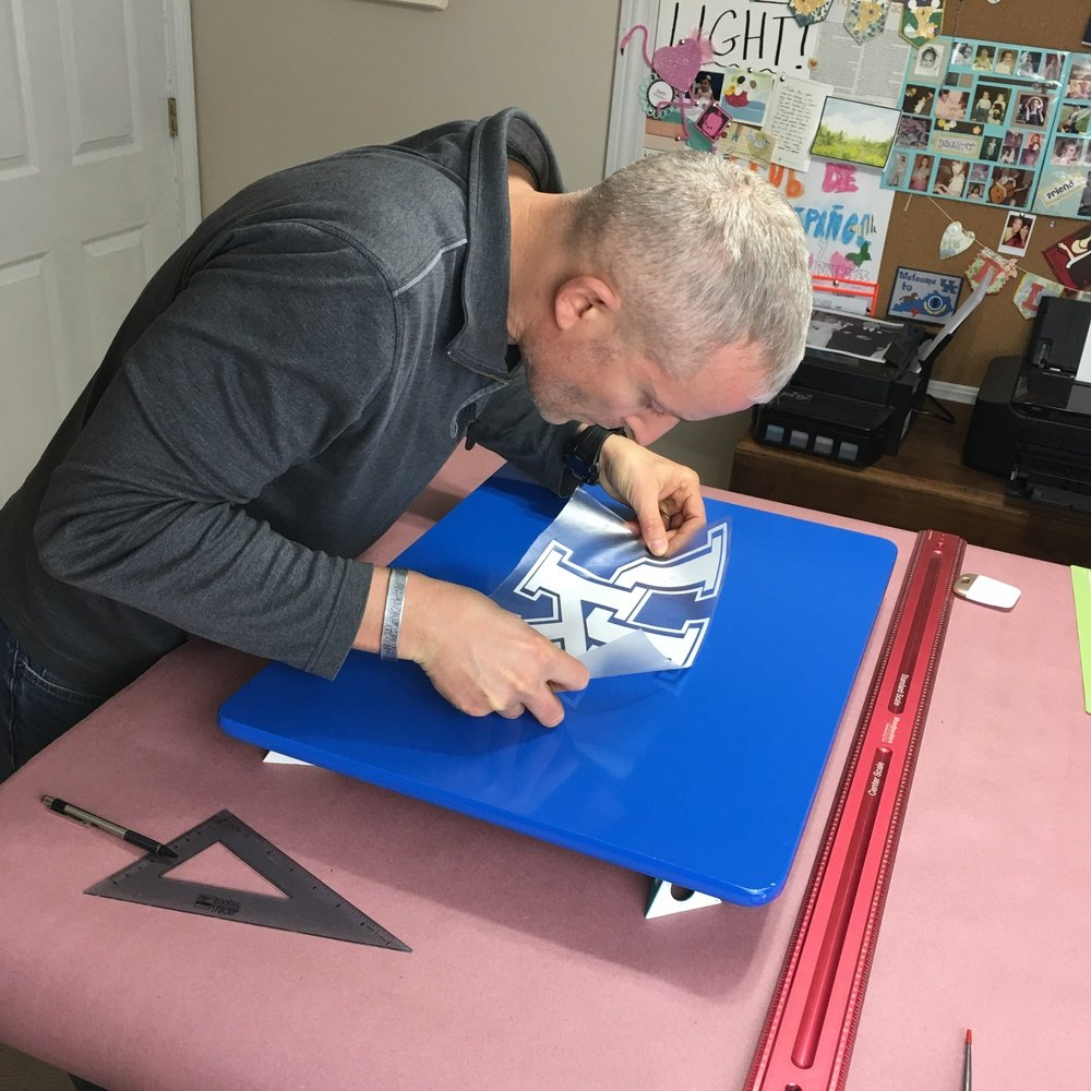 man placing cricut image on kid's desk