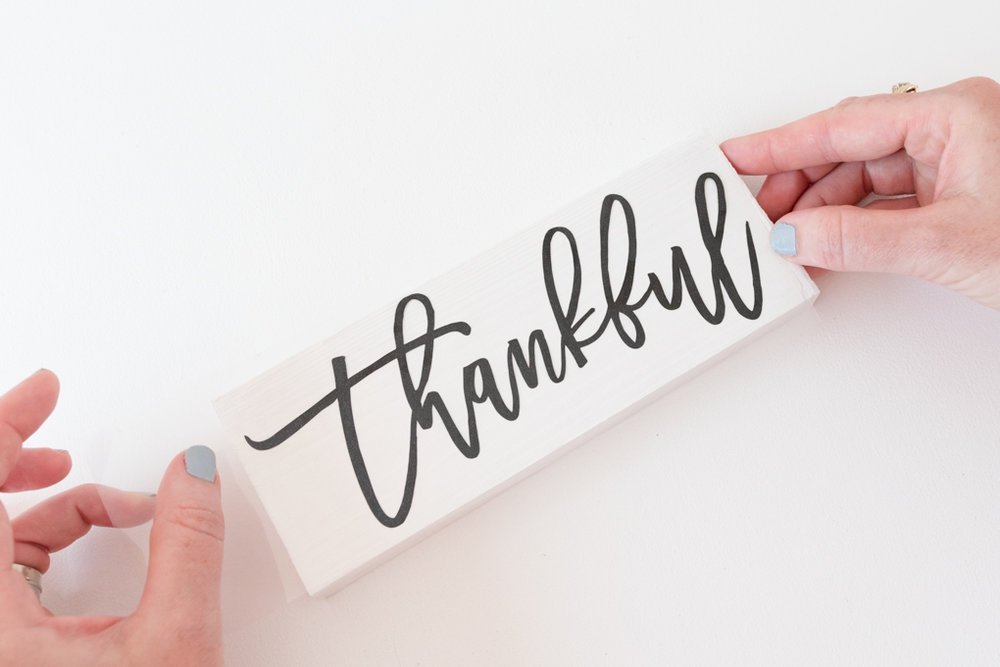woman placing thankful transfer image onto piece of wood