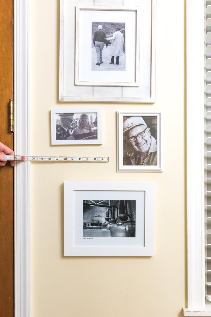woman measuring wall to hang photo