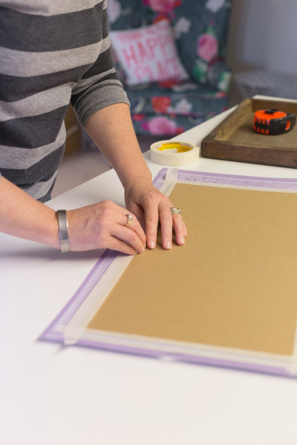 woman taping chipboard to cricut mat