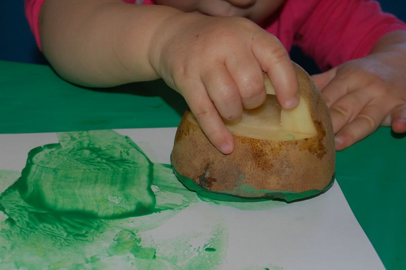 child stamping with potato for potato painting