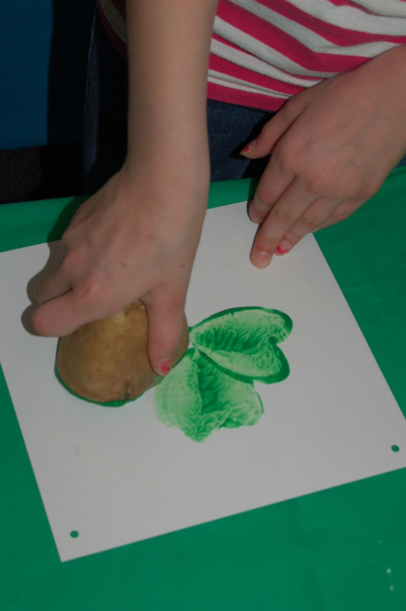child making potato painting of four leaf clover