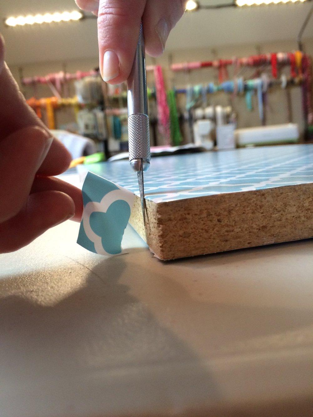 trimming shelf liner paper around shelf