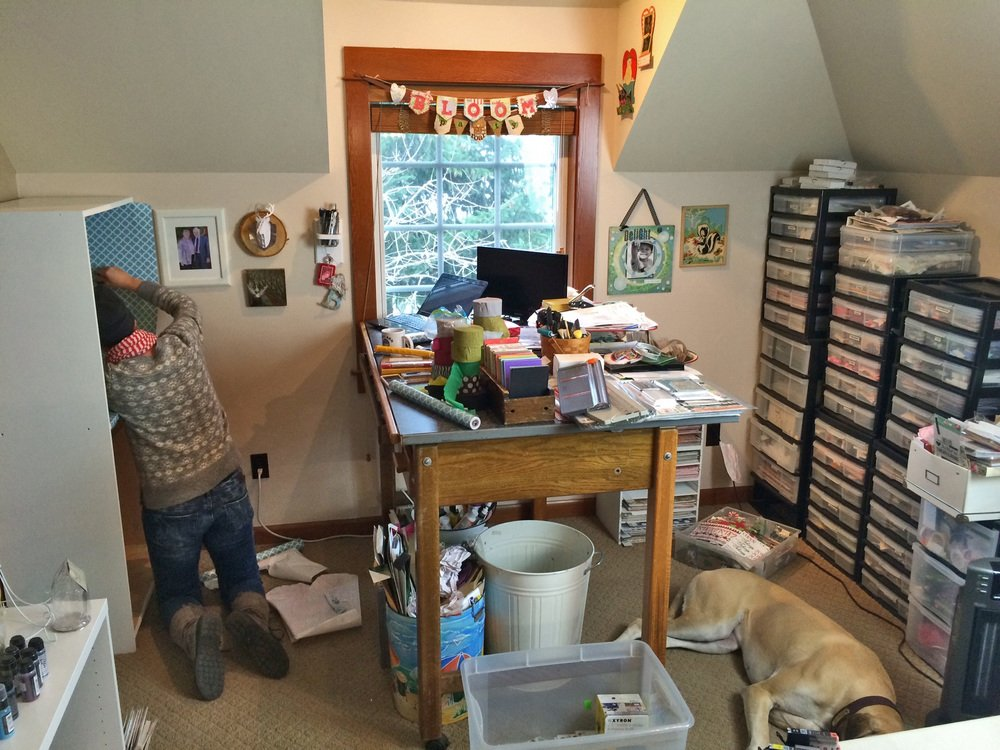 woman in messy craft room with dog