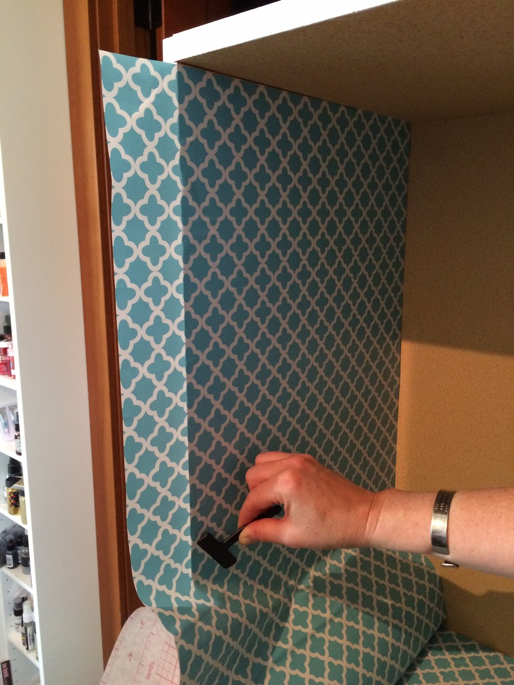adding shelf liner to bookshelf