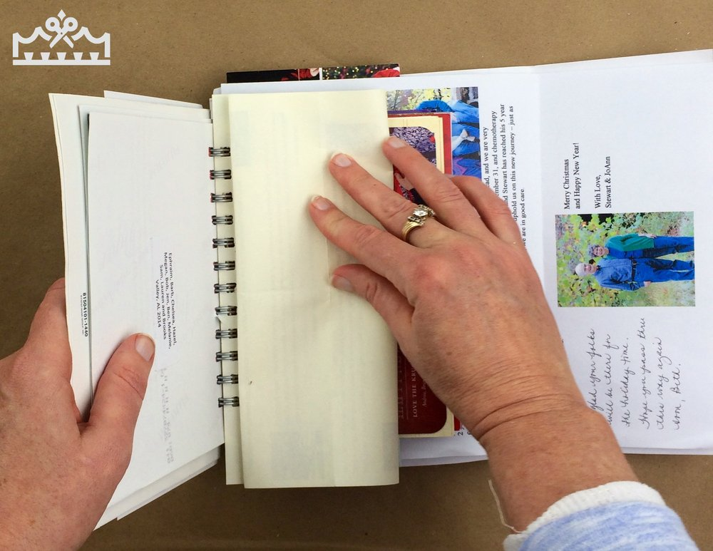 woman folding letters into thirds fro Christmas mini album