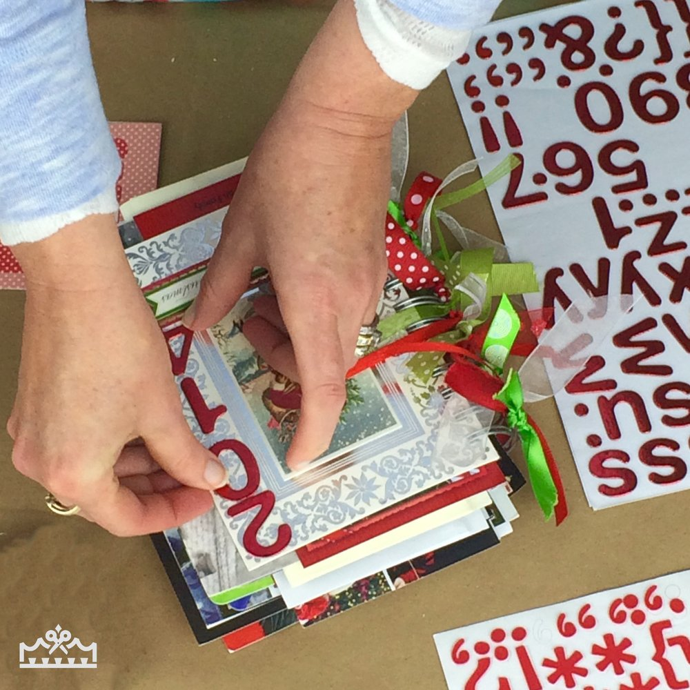 woman adding number stickers to Christmas card mini album