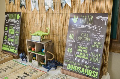dinosaur toys and wooden sign for dinosaur kids party