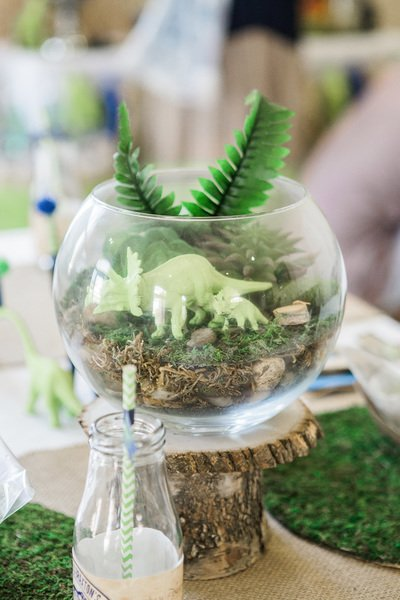 dinosaur party decor with dinosaurs and plants in a vase