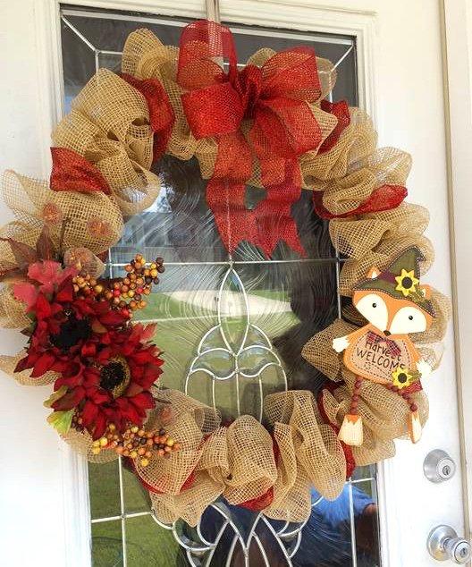 burlap wreath with wooden fox hanging on door