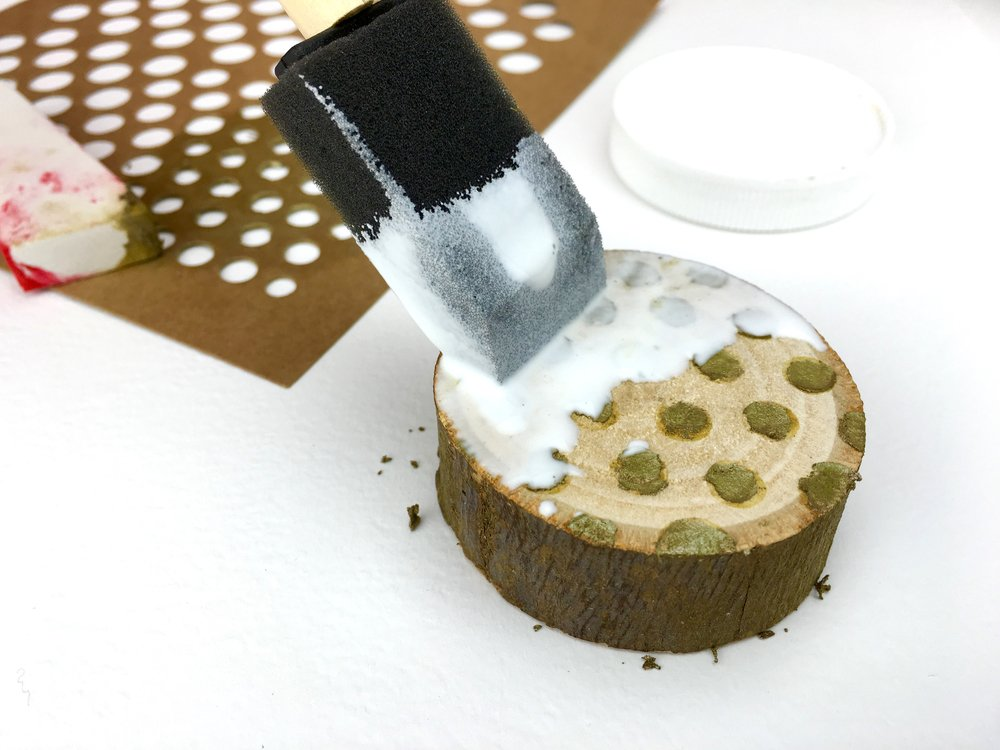 mod podge being added to wooden slice