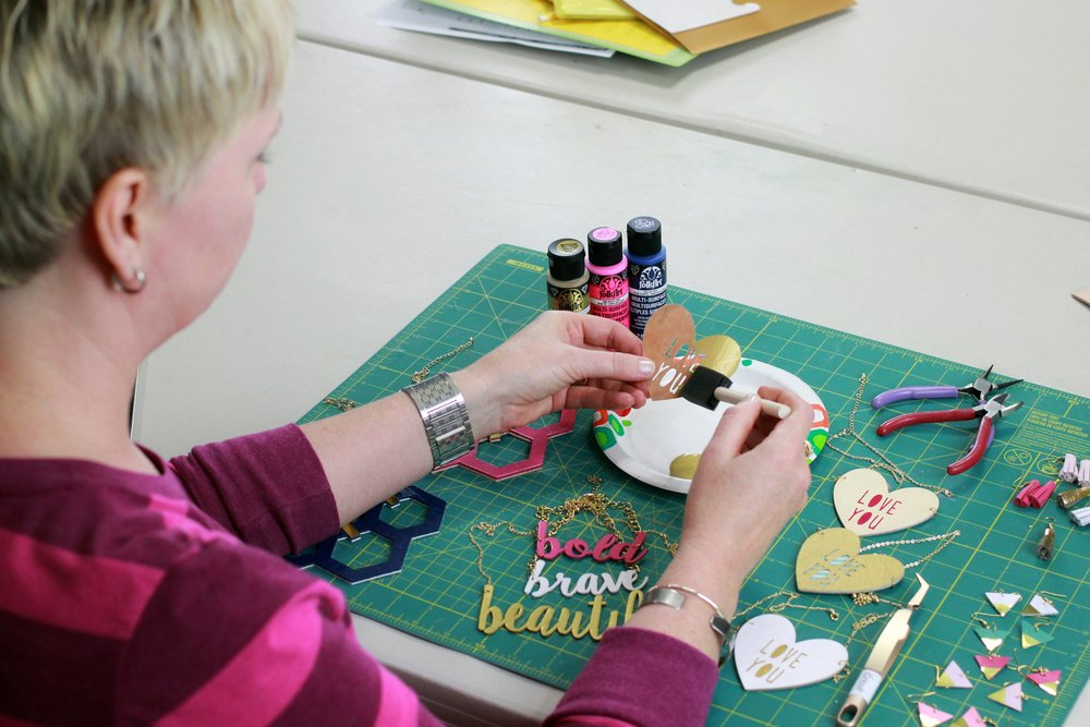 woman making custom necklaces with cricut