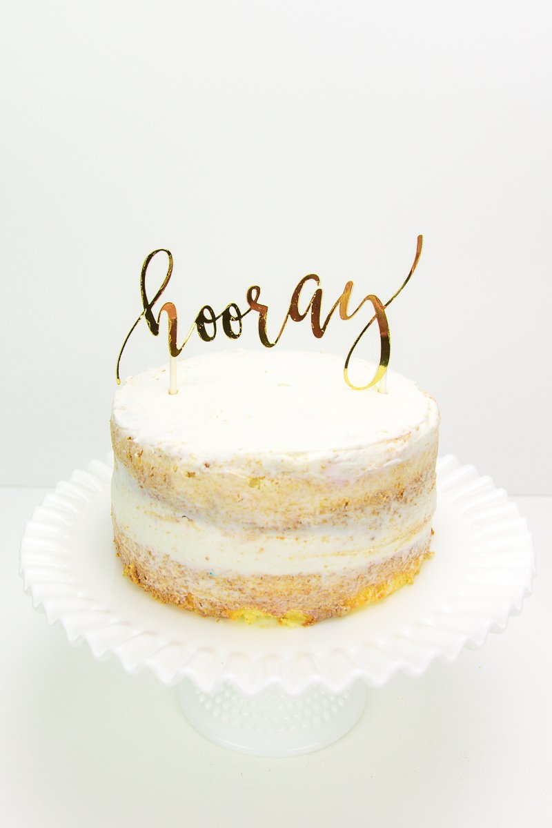 White cake with gold hooray cake topper