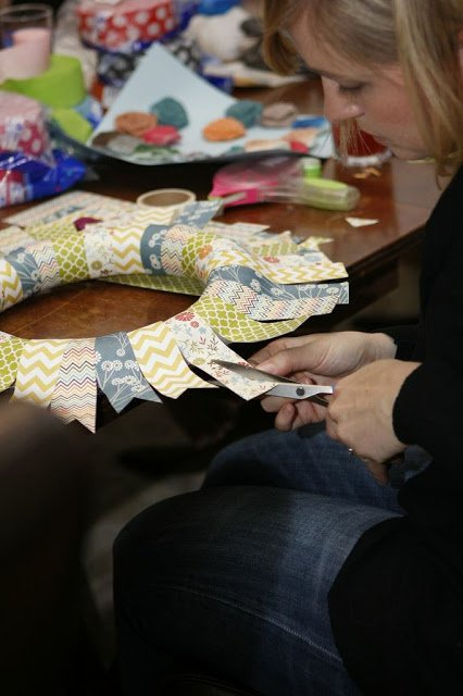woman cutting paper strip for paper wreath craft project