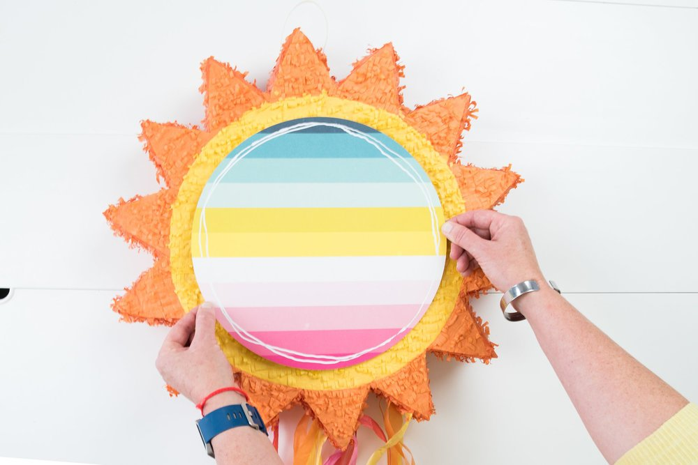 woman gluing paper circle on to sun pinata