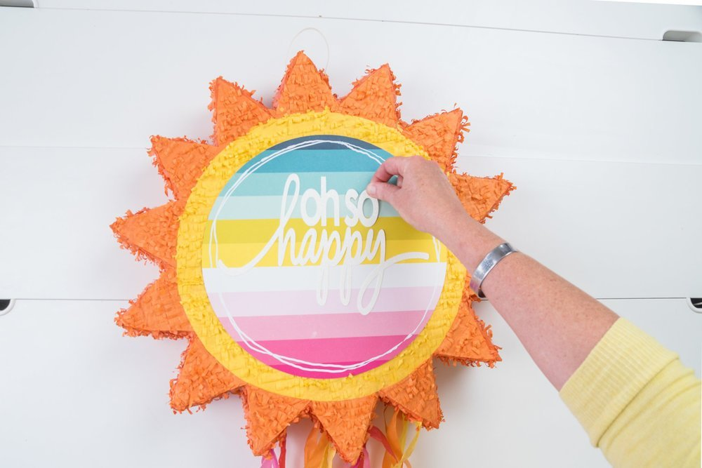 woman adding letters to sun pinata for home decor piece