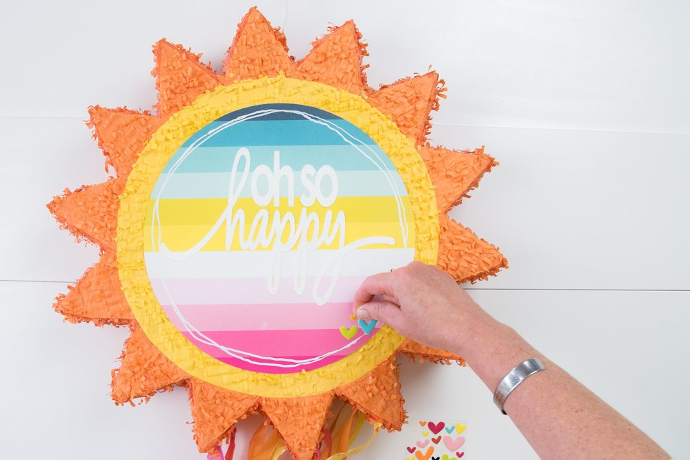 woman adding stickers to sun pinata for home decor piece