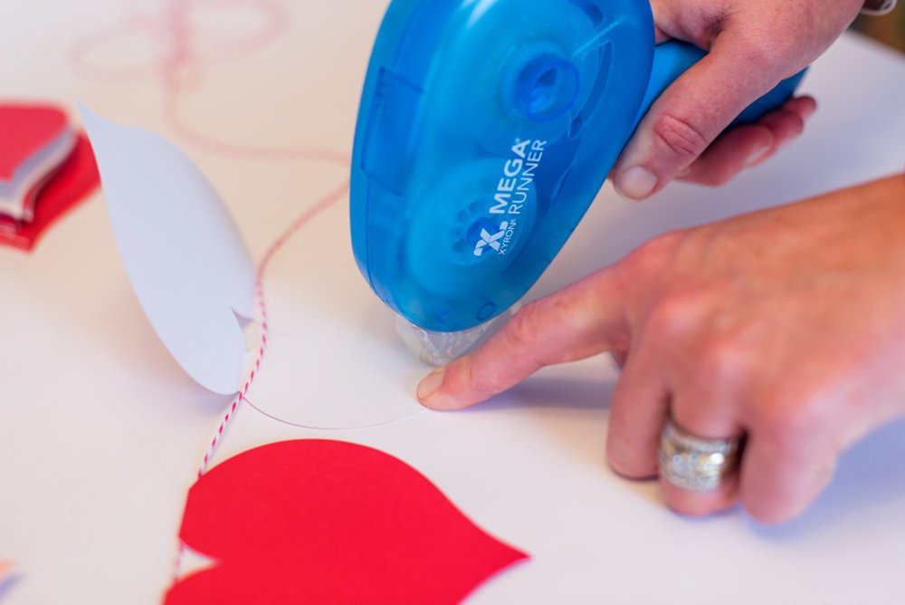 woman using Xyron Mega Runner on Valentine\'s Day project