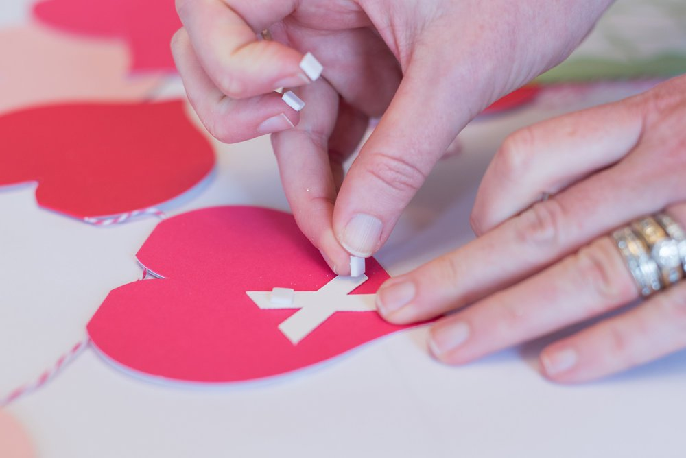 woman adding foam pads to Valentine\'s Day banner