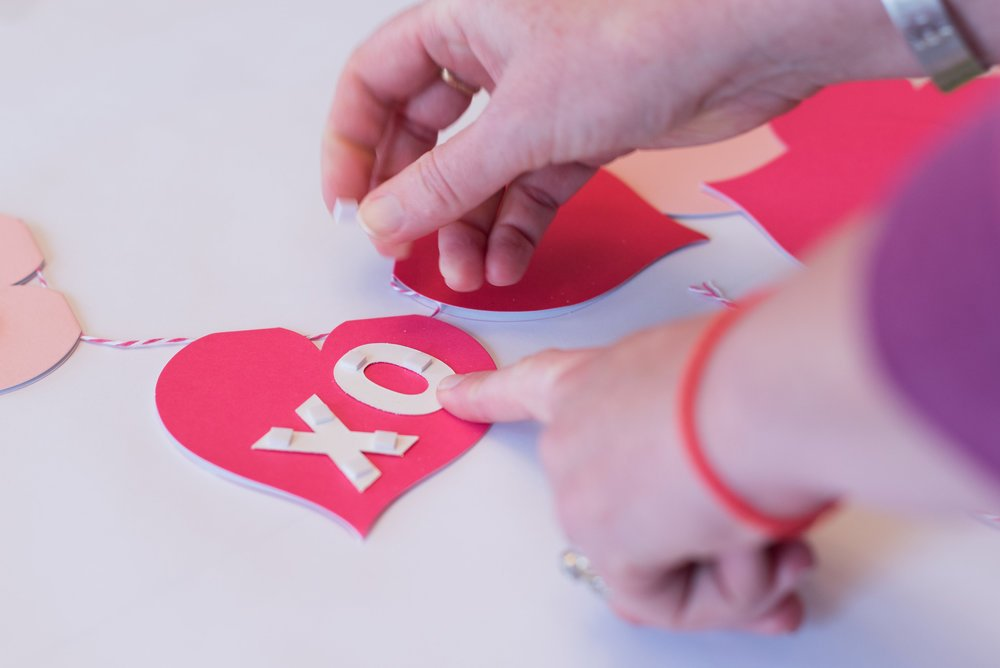 woman adding letter stickers to Valentine\'s banner