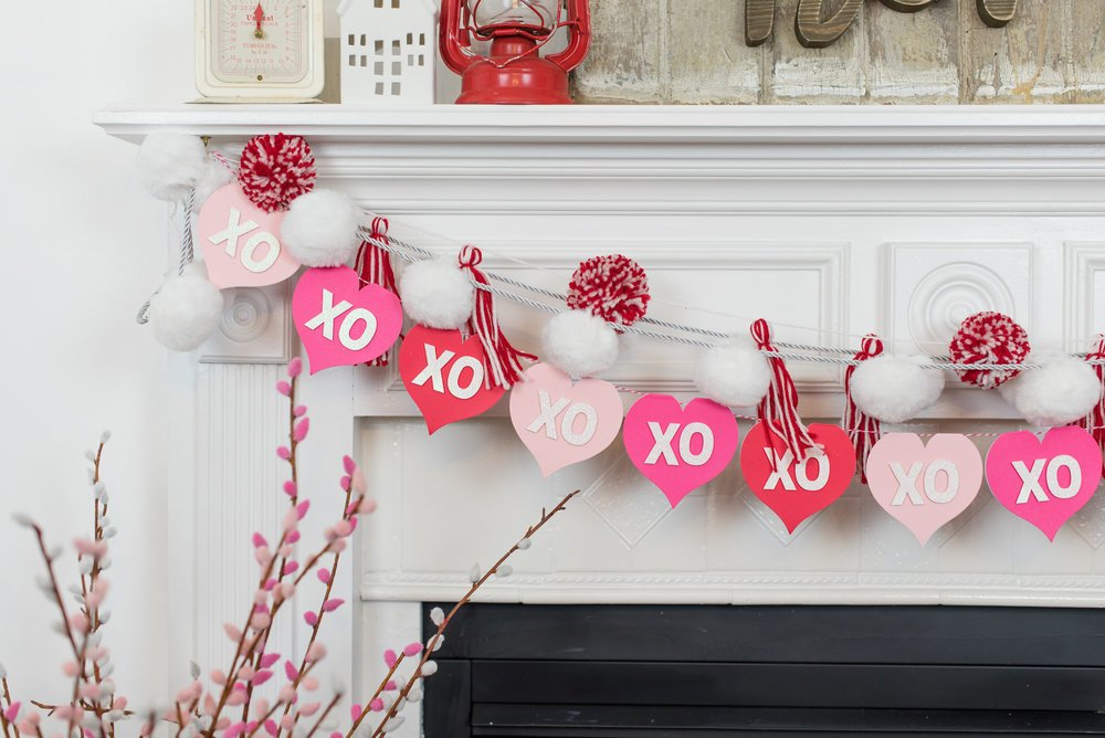 Valentine\'s Day banner hanging on fireplace mantel