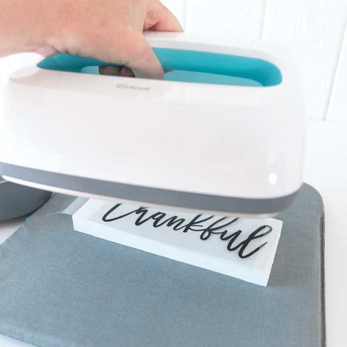 woman using Cricut EasyPress on piece of wood