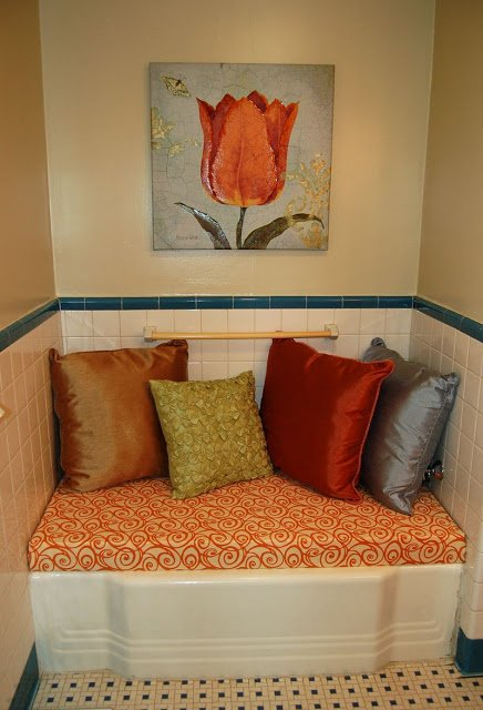 decorative bathroom with bathtub bench covered with pillows