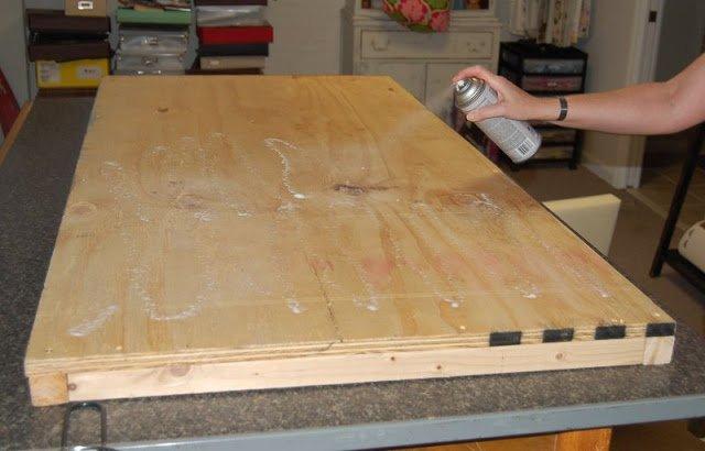 woman applying spray adhesive on wood panel bench top
