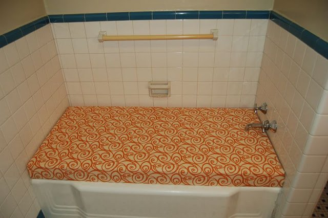 bathtub covered with orange fabric wood bench top