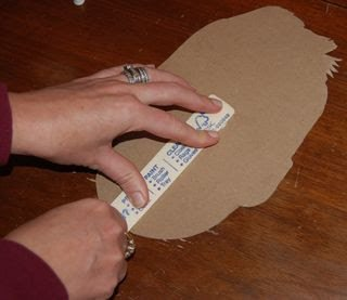 hand pressing down paint stirrer stick onto cardboard cutout