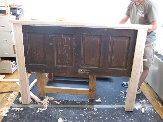 man working on headboard made from old door