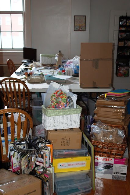 messy studio with craft supplies, boxes, and table