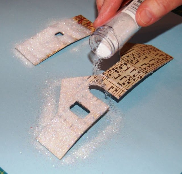 woman adding glitter to Melissa Frances Chipboard House
