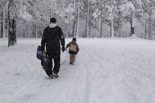 man and child walking in snow