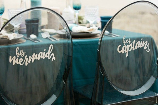 two chairs with writing on the back at a table