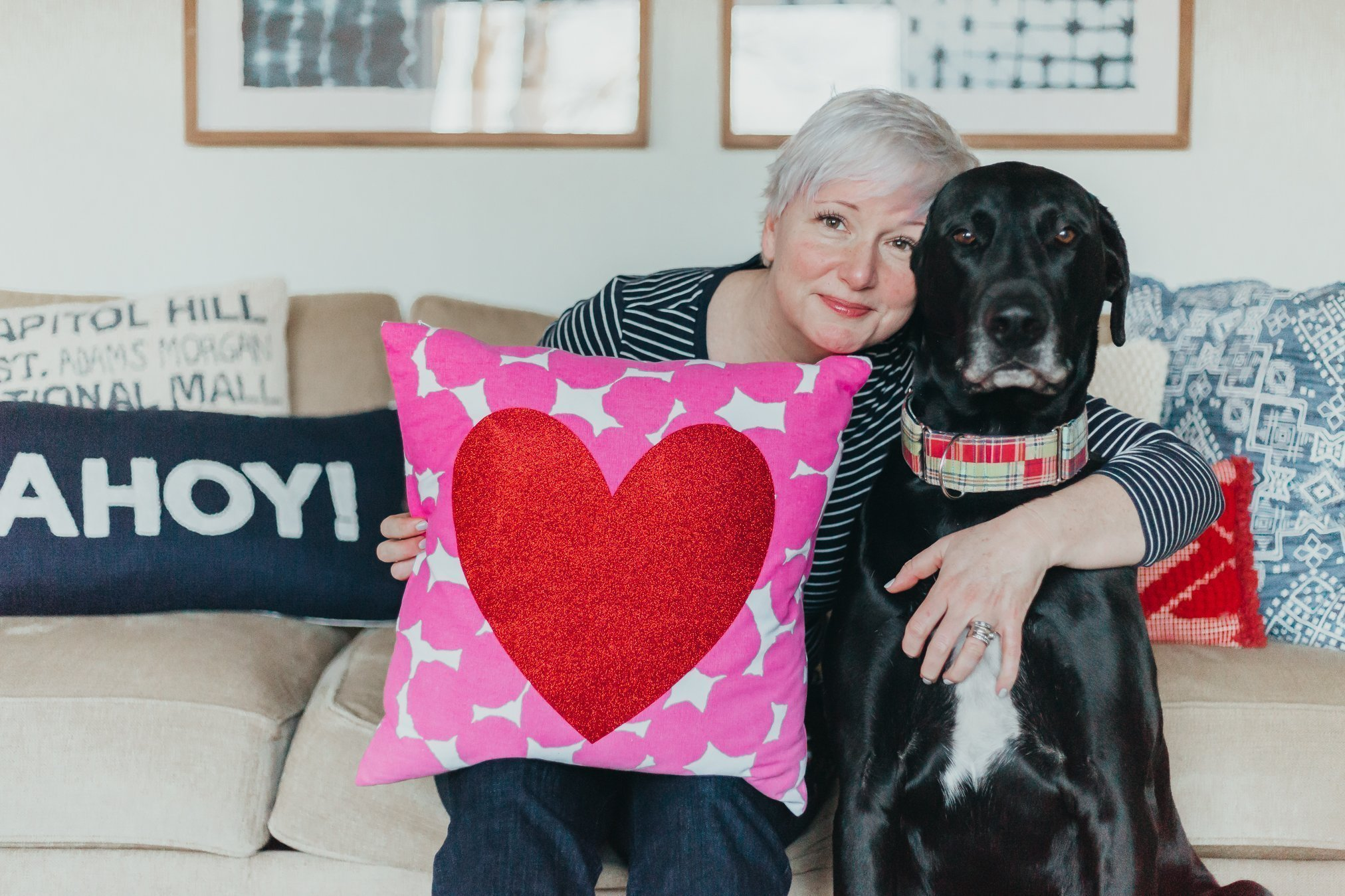 woman holding Valentine's Day pillow and hugging big black dog