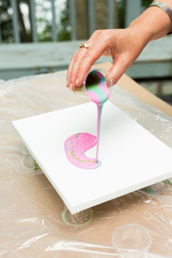 woman pouring paint onto canvas for paint pouring