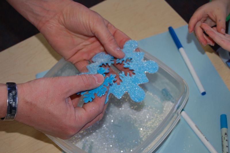 hand punching out middle of snowflake that is covered with glitter