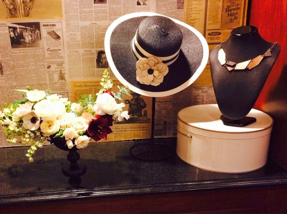 black hat, necklace, and flowers on table
