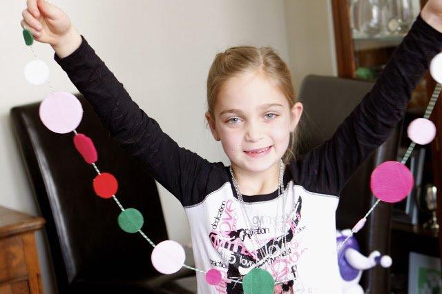 girl smiling and holding felt garland