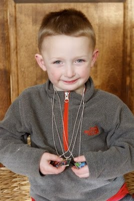 boy smiling and wearing handmade necklaces