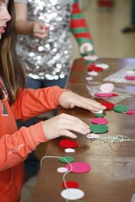 girl sitting at table and creating felt garland