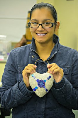woman smiling and holding finished craft project