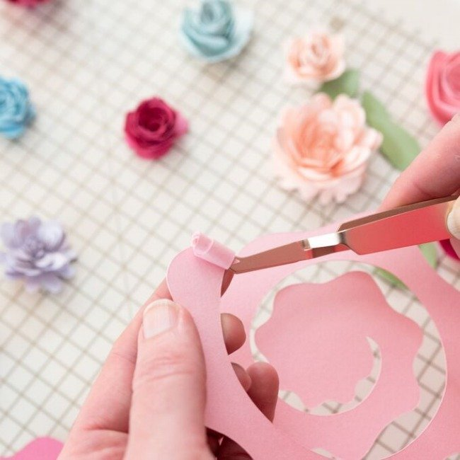 roll the paper flower tightly around the tweezers