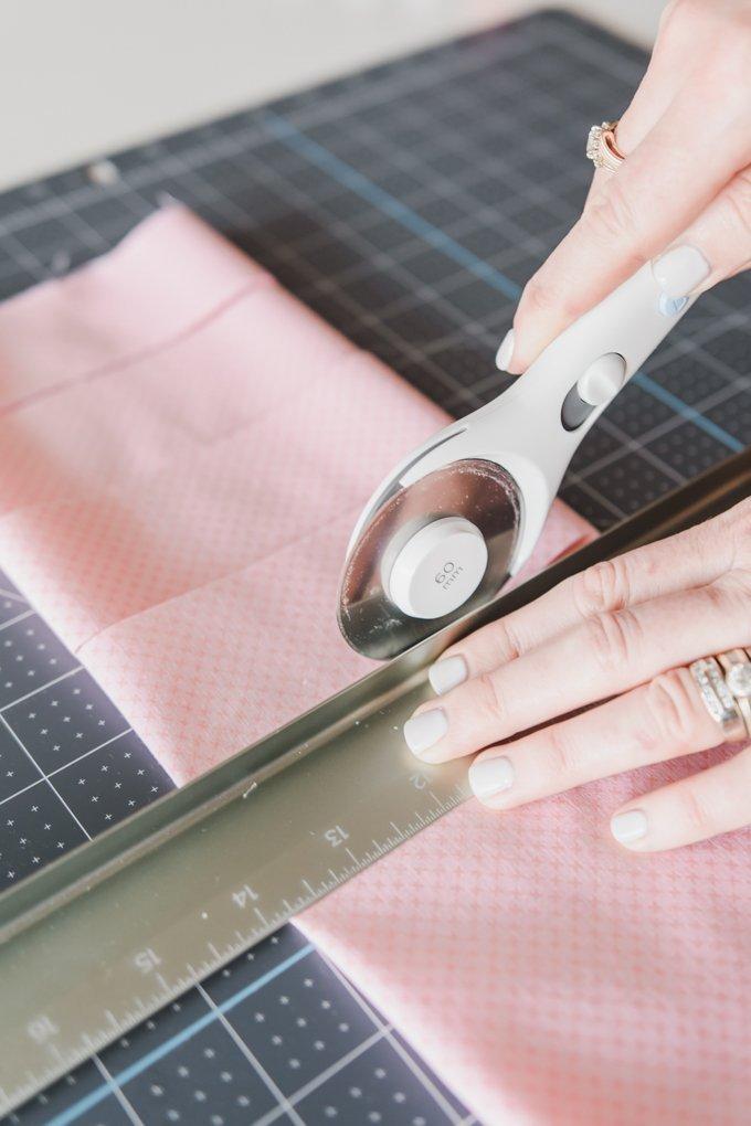 rotary cutter cutting pink fabric strips on self healing mat