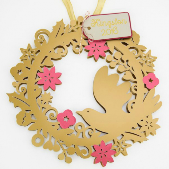 cut out paper wreath with red flowers and a gold dove