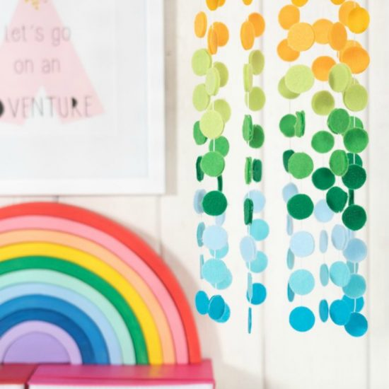 A close up of a colorful wall with a rainbow mobile