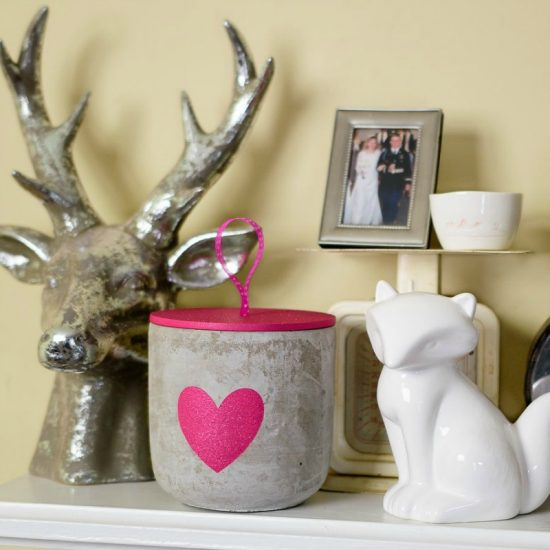 A mantel with a silver deer head and a candle with a heart painted on it