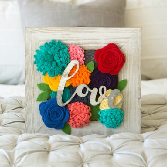 wood frame filled with felt flowers and metal word
