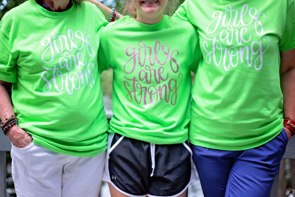 close up of women wearing girls are strong t-shirts